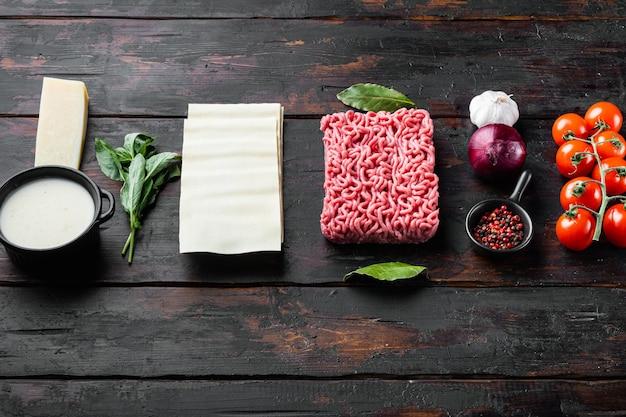 Conjunto de ingredientes diferentes para lasanha, no fundo da velha mesa de madeira escura, com espaço de cópia para o texto