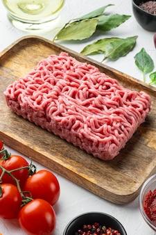 Conjunto de ingredientes do molho à bolonhesa, carne picada, tomate e ervas, na bandeja de madeira, na pedra branca