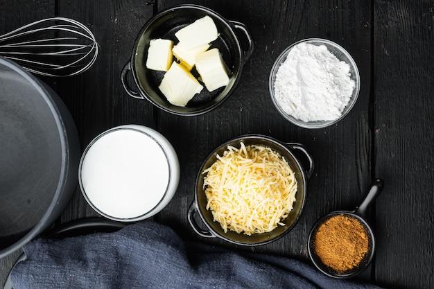 Conjunto de ingredientes do molho bechamel branco, em mesa de madeira preta