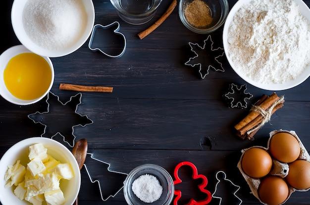 Conjunto de ingredientes para cozinhar biscoitos de gengibre festivos de natal - manteiga, farinha, açúcar, ovos, especiarias com cobertura, formas para biscoitos, corte,