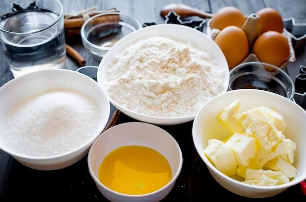 Conjunto de ingredientes para cozinhar biscoitos de gengibre festivos de natal - manteiga, farinha, açúcar, ovos, especiarias com decoração de açúcar, glacê, formas para biscoitos, corte,