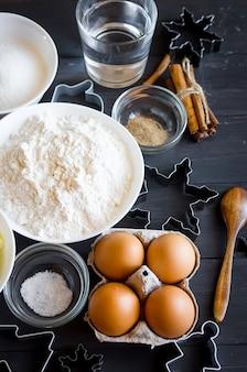 Conjunto de ingredientes para cozinhar biscoitos de gengibre festivos de natal - manteiga, farinha, açúcar, ovos, especiarias com decoração de açúcar, glacê, formas para biscoitos,