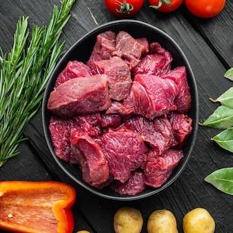 Conjunto de ingredientes para guisado de carne bovina, em mesa de madeira preta, vista de cima plana, formato quadrado