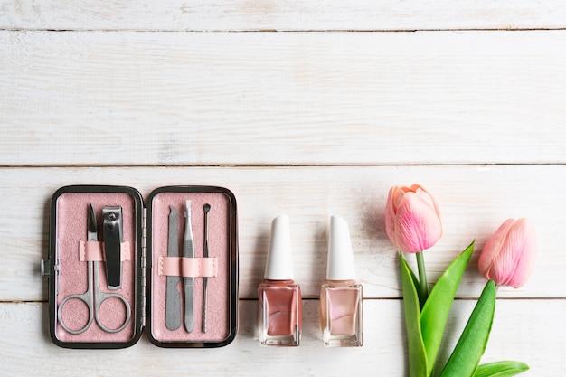 Conjunto de instrumentos e ferramentas de manicure em estojo rosa com esmalte sobre fundo branco de madeira, vista superior, cópia espaço
