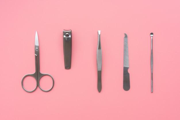 Conjunto de instrumentos e ferramentas de manicure em fundo rosa, vista superior