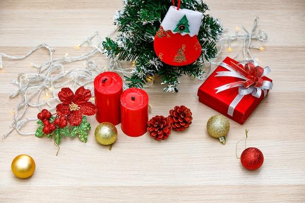 Conjunto de itens decorativos de natal bolas de esfera brilhante brilhante vermelho e dourado velas caixa de presente de presente com fita de prata gravata borboleta corda de lâmpada sementes de pinho árvore de maquete de natal com meia pendurada na mesa de madeira.