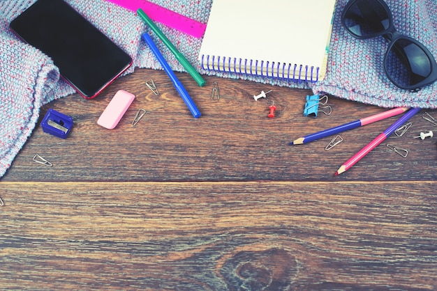 Conjunto de itens escritório móvel caderno desenho lápis marcadores marcadores borracha óculos fundo escuro de madeira
