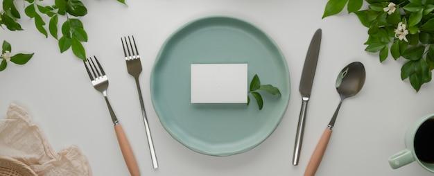 Conjunto de jantar de comemoração com placa de cerâmica turquesa com cartão de lugar branco, talheres e decoração na mesa de jantar branca
