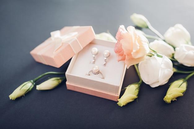 Conjunto de jóias de pérolas em caixa de presente com flores. brincos de prata e anel com pérolas de presente