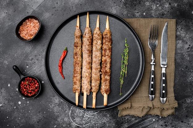 Conjunto de kebab grelhado, na chapa, no fundo da mesa de pedra escura, vista de cima plana