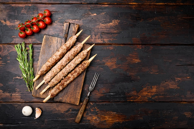 Conjunto de kebabs de tikka, shish e kofta, em fundo de mesa de madeira escura velha, vista de cima plana, com espaço de cópia para o texto