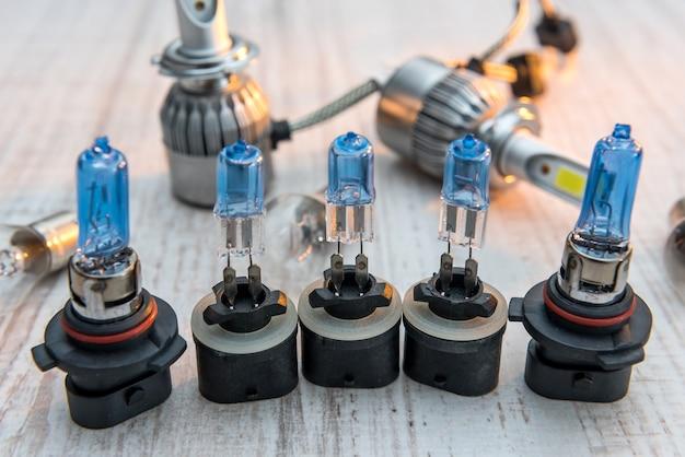 Conjunto de lâmpadas automotivas diferentes para farol de reparo em superfície de madeira branca