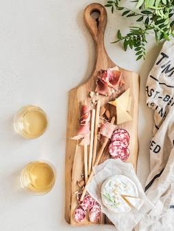 Conjunto de lanche para vinho. variedade de salsichas, azeitonas, queijo, palitos de pão, numa tábua de madeira e dois copos de vinho. postura plana. vista do topo.