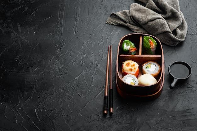 Conjunto de lancheira bentô japonesa com pauzinhos em mesa de pedra preta
