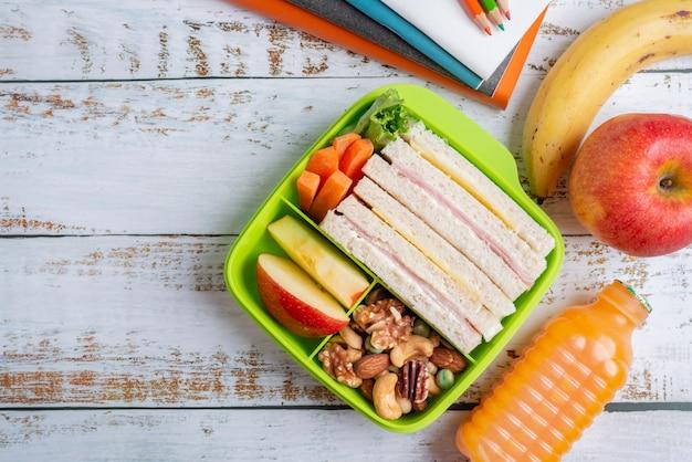 Conjunto de lancheira de sanduíche de queijo presunto com cenoura e castanhas, maçã em caixa, banana e maçã com suco de laranja.