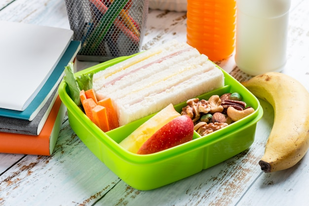Conjunto de lancheira de sanduíche de queijo presunto com cenoura e castanhas, maçã em caixa, banana e suco de laranja com leite.