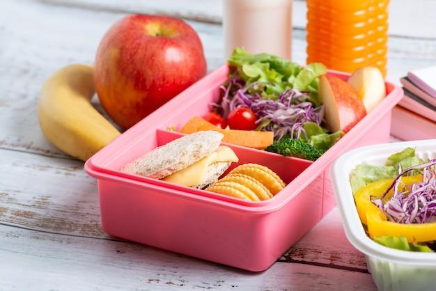 Conjunto de lancheira saudável de queijo sanduíche com biscoito e salada em caixa, banana e maçã, suco de laranja e leite.