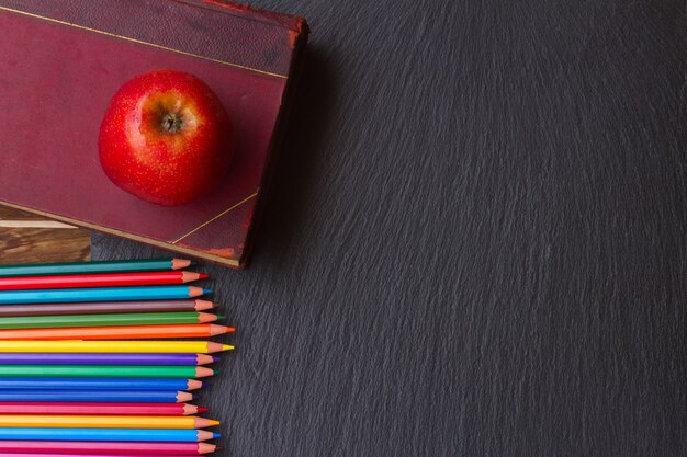 Conjunto de lápis coloridos com bebida velha e maçã no quadro negro