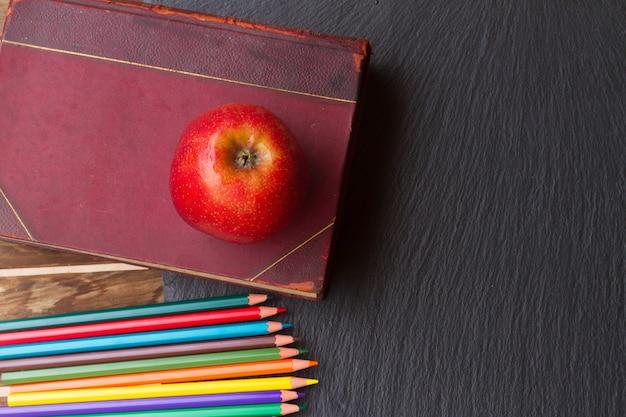 Conjunto de lápis coloridos com livro vintage e maçã vermelha no quadro preto