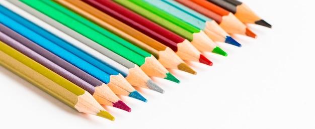 Conjunto de lápis de cor em um fundo branco. de volta ao conceito de escola. lugar para texto. formato de banner