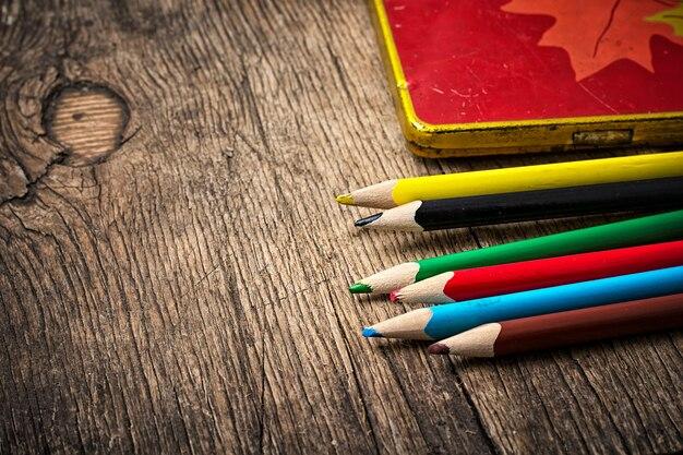 Conjunto de lápis de cor sobre fundo de madeira desfeita