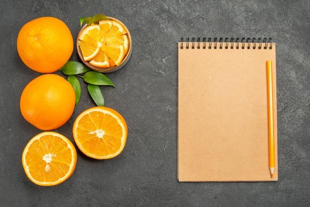 Conjunto de laranjas amarelas inteiras e picadas e caderno na mesa escura