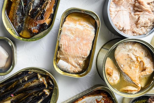 Conjunto de latas de alumínio e lata com saury, cavala, espadilha, sardinha, sardinha, lula, atum sobre mesa texturizada branca close-up.