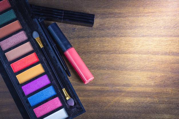 Conjunto de lay plana (vista superior) de maquiagem cosméticos em madeira