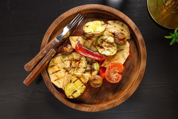 Conjunto de legumes assados, abobrinha, tomate, batata, pimentão na placa de madeira