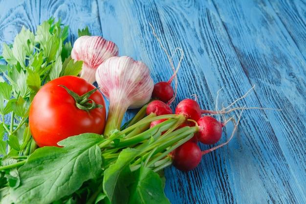 Conjunto de legumes com alho, tomate e rabanete na superfície de madeira