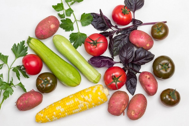 Conjunto de legumes e raminhos de manjericão e salsa. batatas, espiga de milho, tomate e abobrinha em branco. postura plana