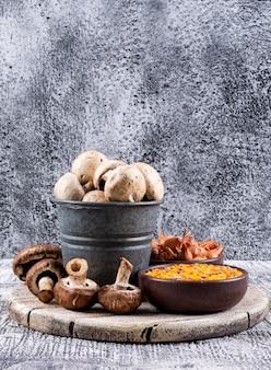 Conjunto de lentilhas, cebolas pequenas em tigelas e cogumelos marrons e brancos em uma tigela e um balde