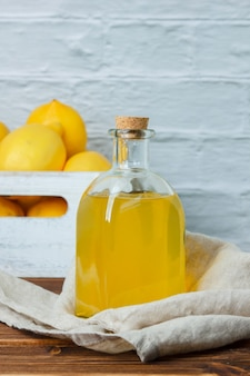 Conjunto de limões em uma caixa de madeira e suco de limão em uma superfície de madeira. vista lateral. espaço para texto