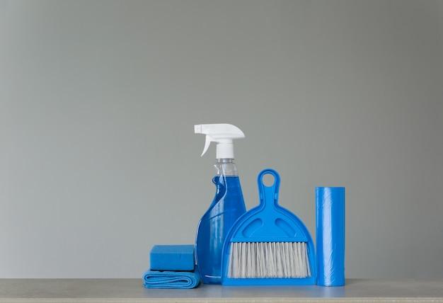 Conjunto de limpeza azul em fundo neutro: detergente de pulverização, sacos de lixo, panos de pó, esponja, colher e vassoura. copie o espaço.