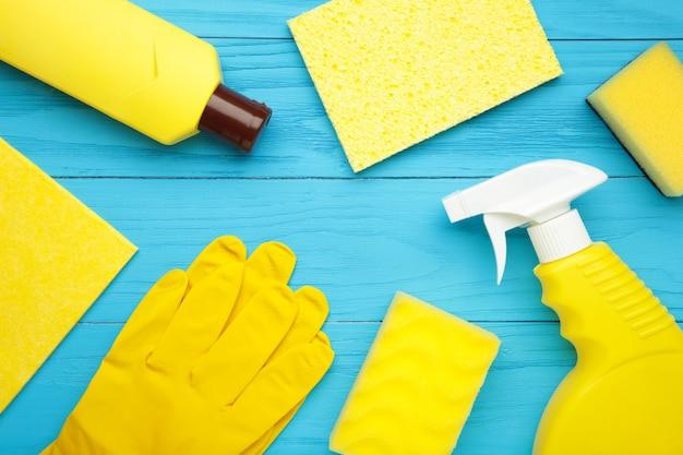 Conjunto de limpeza. ferramentas para limpeza. agentes de limpeza, spray, luvas de borracha na parede azul. postura plana