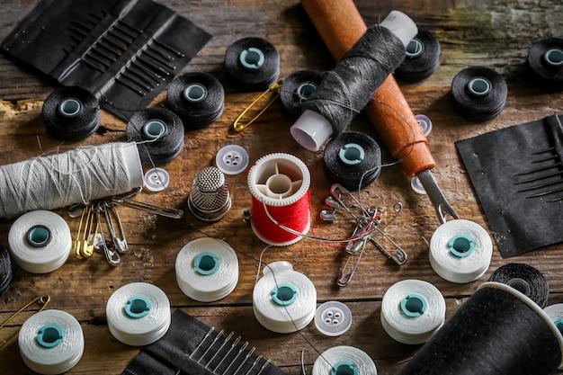 Conjunto de linhas de costura e acessórios na mesa de madeira