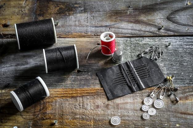 Conjunto de linhas de costura e acessórios na parede de madeira
