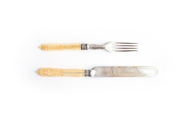 Conjunto de louça vintage. faca e garfo com alças de osso em um branco. vista do topo.