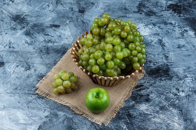 Conjunto de maçã e uvas verdes em uma cesta em grunge e pedaço de fundo de saco. vista de alto ângulo.