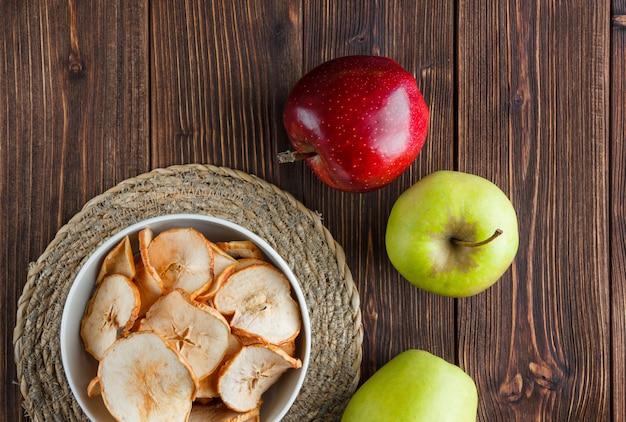 Conjunto de maçã fresca e maçãs secas em uma tigela sobre um pano e fundo de madeira. vista do topo.