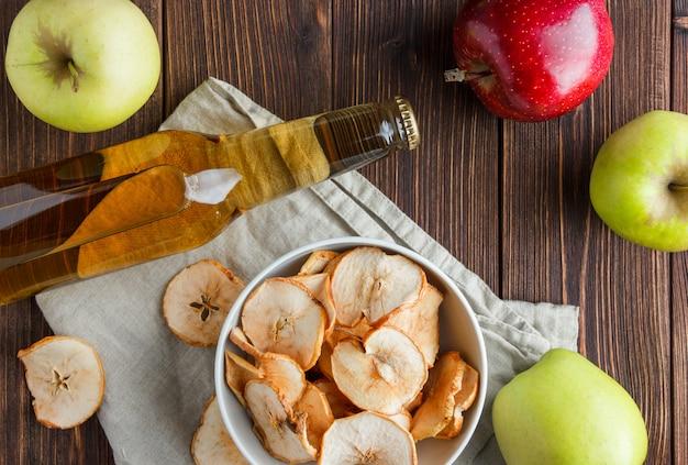 Conjunto de maçã fresca e suco e maçãs secas em uma tigela sobre um pano e fundo de madeira. vista do topo.