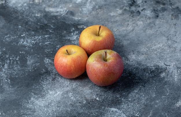 Conjunto de maçã vermelha fresca amarela sobre fundo de mármore.