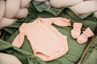 Conjunto de macacão de bebê dentro do berço