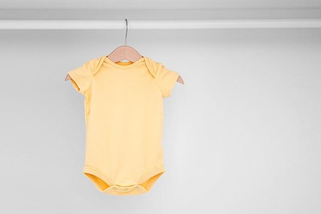 Conjunto de macacões de bebê para uma menina recém-nascida e um menino em cabides no guarda-roupa branco. maternidade, limpar o guarda-roupa dos filhos em casa. conceito de moda mínimo.