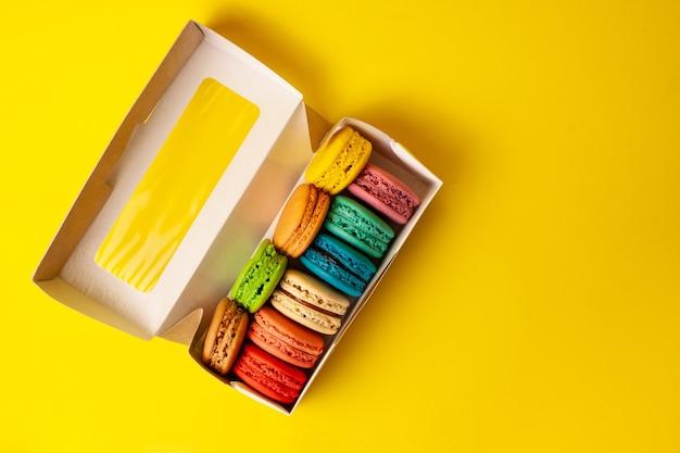 Conjunto de macaroons de cookies franceses diferentes em uma caixa de papel. vista do topo.