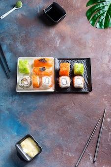 Conjunto de maki roll e folhas verdes palm na mesa de pedra.