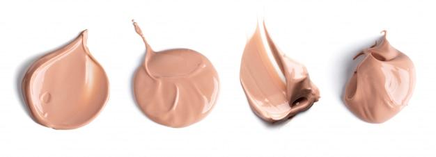 Conjunto de manchas delicadamente bege da base cremosa de maquiagem, isolada no fundo branco. corretivo cosmético. textura de creme marrom realista para maquiagem.