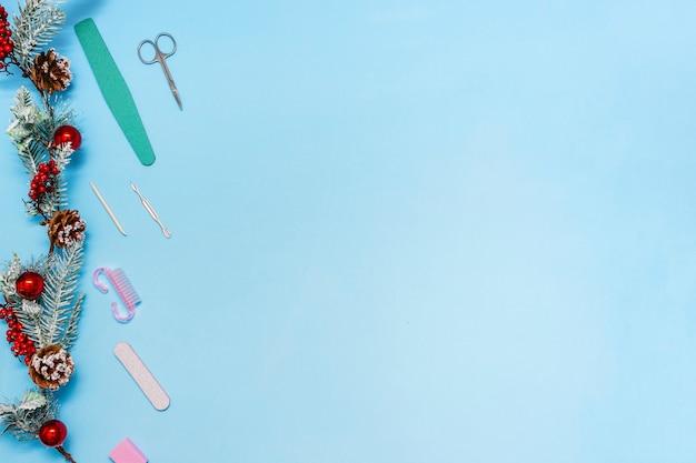 Conjunto de manicure com um ramo de abeto decorado com bolas em um azul