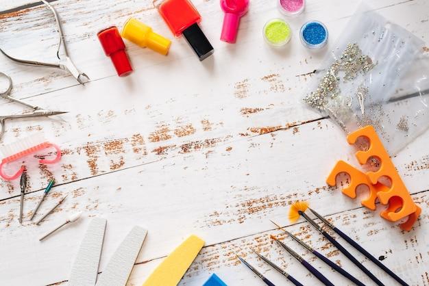 Conjunto de manicure e esmaltes em uma madeira branca. com espaço para seu texto