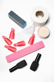 Conjunto de manicure. ferramentas, lixa de unha, esmalte em gel, pó acrílico em um fundo branco. foto de close